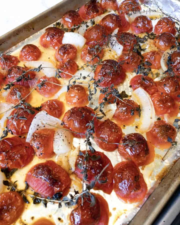 Oven roasted tomatoes, garlic, onion and herbs on a baking sheet